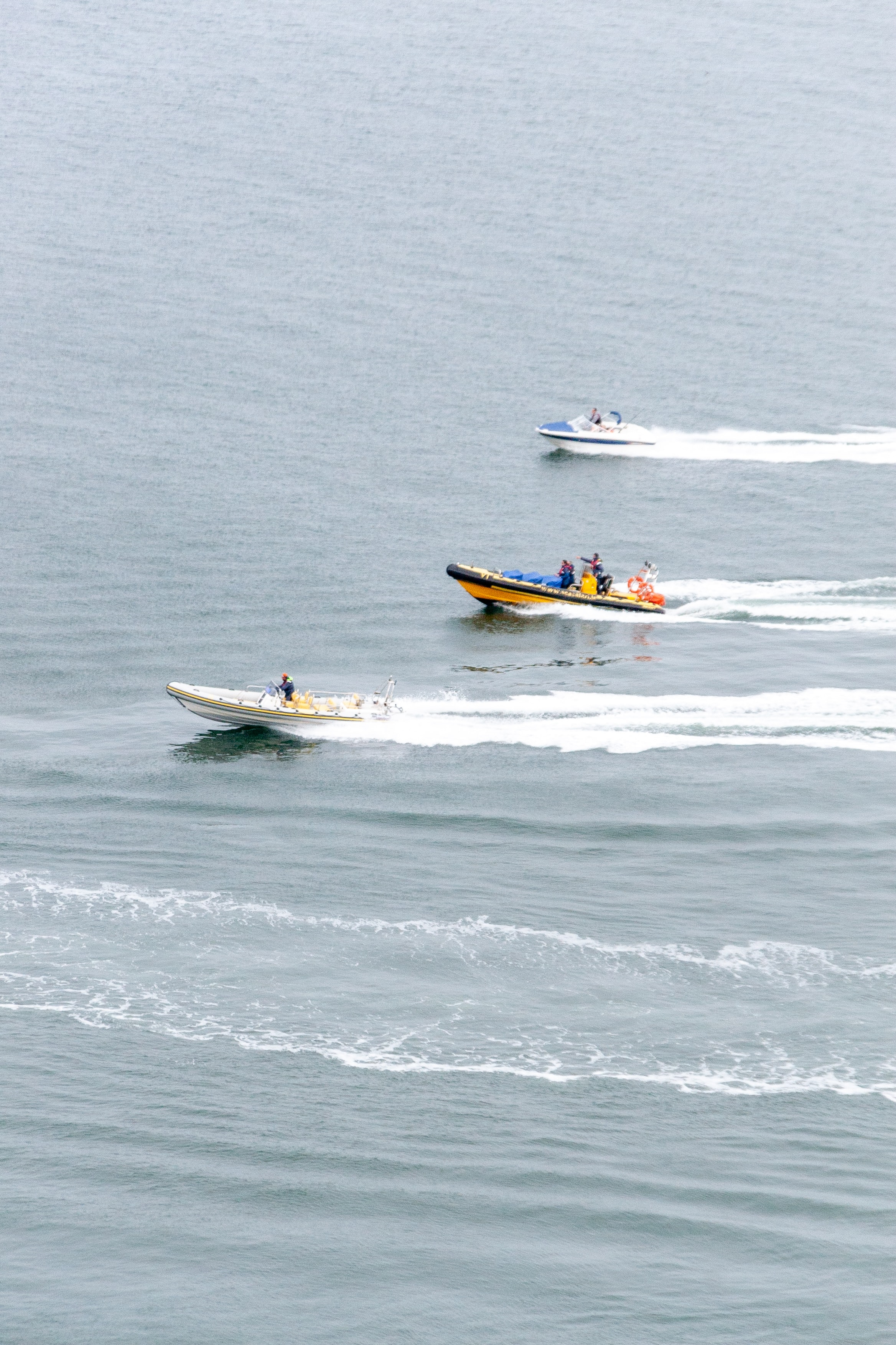 Three Marine Boats racing out on the waters