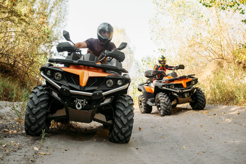Two people riding four-wheelers